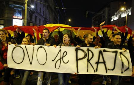 """Participants hold a rainbow flag and a placard, which reads: """"This is Pride"""", as they march next to a riot policeman through the streets of downtown Belgrade September 27, 2013. REUTERS/Marko Djurica"""