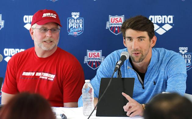 Michael Phelps, right, speaks to the media after practice as coach Bob Bowman listens Wednesday, April 23, 2014, in Mesa, Ariz. Phelps is competing in the Arena Grand Prix at Mesa on Thursday as he re