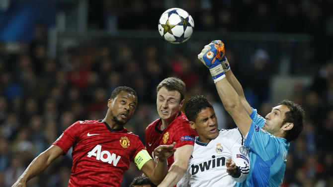 Manchester United's Patrice Evra, left, and Jonny Evans contest a high ball with Real Madrid's Raphael Varane from France and goalkeeper Diego Lopez, right, during the Champions League round of 16 first leg soccer match between Real Madrid and Manchester United at the Santiago Bernabeu stadium in Madrid, Wednesday Feb. 13, 2013. (AP Photo/Andres Kudacki)