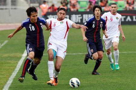 Japan's Maeda and Uchida fight for the ball with Jordan's Morjan and al-Saify during their 2014 World Cup qualifying soccer match at King Abdullah stadium in Amman