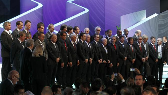 Blatter joins soccer coaches for a group photo during the draw for the 2014 World Cup in Sao Joao da Mata