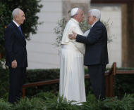 Pope Francis and Palestinian President Mahmoud Abbas embrace each other as Israel's President Shimon Peres, left, looks at them during an evening of peace prayers in the Vatican gardens, Sunday, June 8, 2014. Pope Francis waded head-first into Mideast peace-making Sunday, welcoming the Israeli and Palestinian presidents to the Vatican for an evening of peace prayers just weeks after the last round of U.S.-sponsored negotiations collapsed. (AP Photo/Gregorio Borgia)