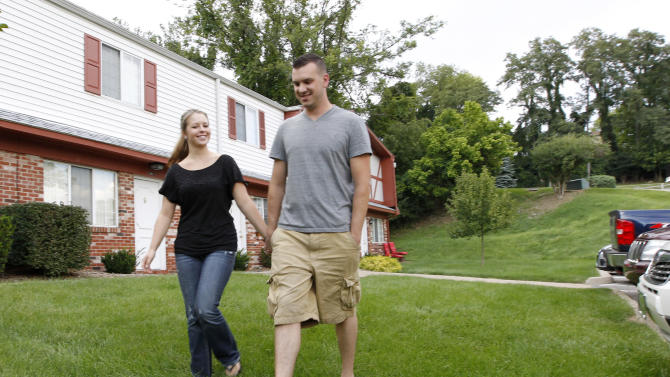 "In this Monday, Aug. 20, 2012 photo, Marine Sgt. Ron Strang, right, walks with his girlfriend, Monica Michna, in the yard by his home in Jefferson Hills, Pa., just south of Pittsburgh. In 2008, the federal government created AFIRM, the Armed Forces Institute of Regenerative Medicine, a network of top hospitals and universities around the country, and gave $300 million in grants to spur new treatments using cell science and advanced plastic surgery. Strang is among those benefiting. The 28-year-old former Marine sergeant from Pittsburgh lost half of his left thigh muscle to shrapnel, leaving too little to stabilize his gait. ""My knee would buckle and I'd fall over,"" he said. Now, after an experimental cell treatment at the University of Pittsburgh Medical Center, ""I'm able to run a little bit"" and play a light football game with friends, he said. ""It's been a huge improvement."" (AP Photo/Keith Srakocic)"