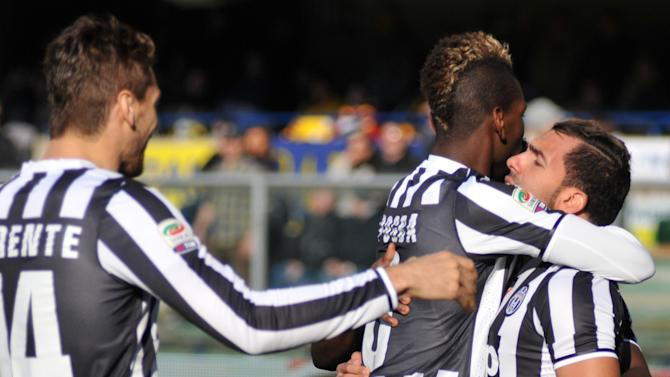 Juventus' forward Carlos Tevez, right, of Argentina, is hugged by his teammate Paul Pogba, of France, after he scored during a Serie A soccer match against Hellas Verona at the Bentegodi stadium in Verona, Italy, Sunday, Feb. 9, 2014