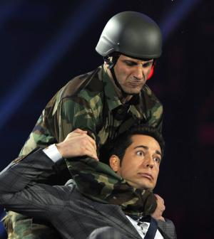 U.S. soldier Daniel Aldema, background, and host Zachary Levi are seen onstage at Spike TV's Video Game Awards on Saturday, Dec. 10, 2011, in Culver City, Calif. (AP Photo/Chris Pizzello)