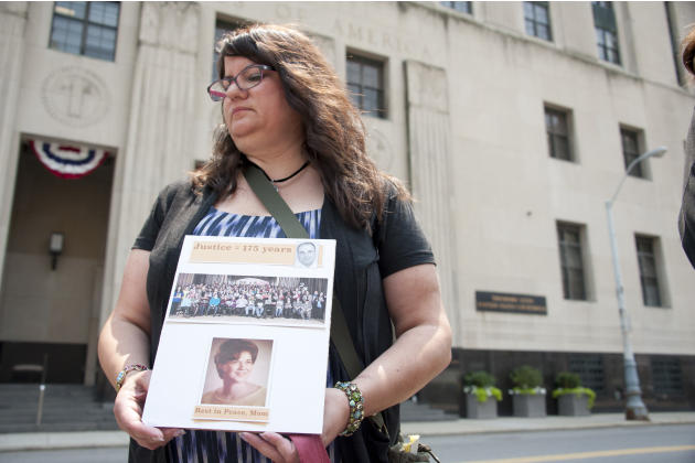 Liz Lupo, of Lake Orion, Mich., holds a sign memorializing her mother, who died while under Dr. Fata's care, outside the federal courthouse in downtown Detroit, Monday July 6, 2015. Fata is headed
