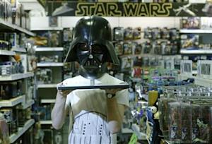 Employee Simon Domoney poses with a scale replica of Star Wars character Darth Vader's helmet at the Forbidden Planet memorabilia and comic store in London