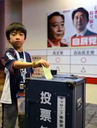 A boy casts a mock vote in a straw poll at the Kidzania career theme park in Tokyo. Commentators say that in a nation with one of the world's oldest populations, mainstream parties like the LDP have little incentive to cater to the young