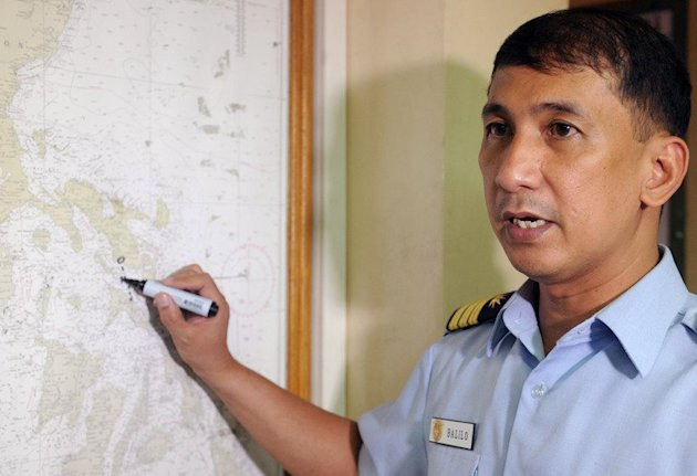 Philippine coastguard spokesman Commander Arman Balilo points to the area on a map where a ferry went down in clam weather on June 14, 2013. Philippine navy divers battled strong ocean currents in a desperate hunt for seven missing passengers