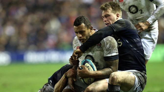 England's Courtney Lawes, left, is tackled by Scotland's Stuart Hogg, right, during their Six Nations rugby union international match at Murrayfield, Edinburgh, Scotland, Saturday Feb. 8, 2014. (AP Photo/Scott Heppell)