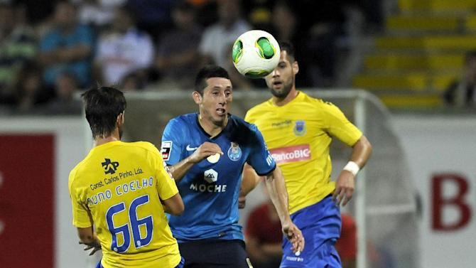 FC Porto's Hector Herrera, from Mexico, drives the ball past Arouca's Nuno Coelho, left, during their Portuguese League soccer match at the Municipal Stadium, in Arouca, Portugal, Sunday Oct. 6, 2013