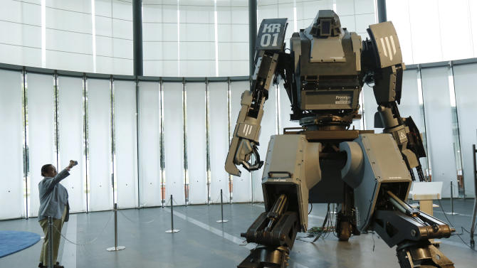 "A man takes a picture of a giant ""Kuratas"" robot at an exhibition in Tokyo"