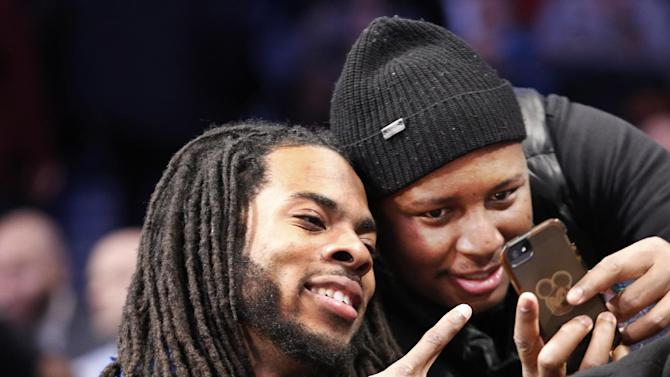 Seattle Seahawks cornerback Richard Sherman, left, gestures as a fan takes a photo with him during the first half of the Toronto Raptors NBA basketball game against the Brooklyn Nets at the Barclays Center, Monday, Jan. 27, 2014, in New York