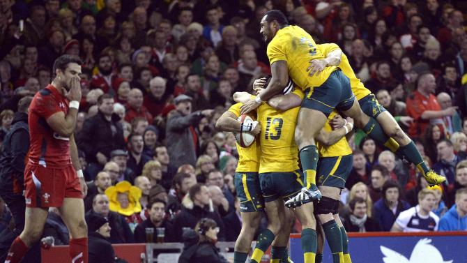 Australian players jump on top of Christian Lealiifano after he scored a try against Wales during their international rugby union match in Cardiff