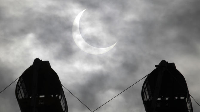 An annular solar eclipse is seen between Ferris wheel in the sky over Yokohama near Tokyo Monday, May 21, 2012.  The annular solar eclipse, in which the moon passes in front of the sun leaving only a golden ring around its edges, was visible to wide areas across the continent Monday morning. (AP Photo/Koji Sasahara)