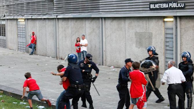 In this May 17 2015 photo, a young boy runs away as a riot policeman restrains his father outside of a stadium, in Guimaraes, Portugal, Sunday, May 17, 2015. At right, the man's older son and father are led away by other policemen. Portuguese prosecutors are investigating a policeman who beat a man in front of his young children and punched their grandfather outside a soccer stadium, sparking a national scandal. Police approached Jose Magalhaes, his two sons and his father Sunday outside Guimaraes stadium, where Benfica had just won the Portuguese league title, according to film footage and witness reports. (AP Photo/Delfim Machado)