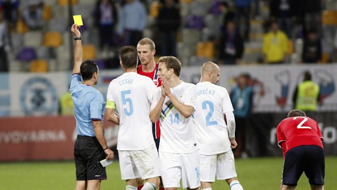 Norway's Brede Hangeland receives a yellow card during the 2014 World Cup group E qualifier soccer match between Slovenia and Norway in Maribor, Slovenia, Friday, Oct 11, 2013