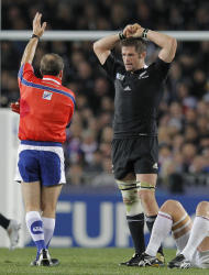 Referee Alain Rolland, left, signals a penalty as New Zealand All Blacks captain Richie McCaw looks on during their Rugby World Cup game against France at Eden Park in Auckland, New Zealand, Saturday, Sept. 24, 2011. (AP Photo/Christophe Ena)