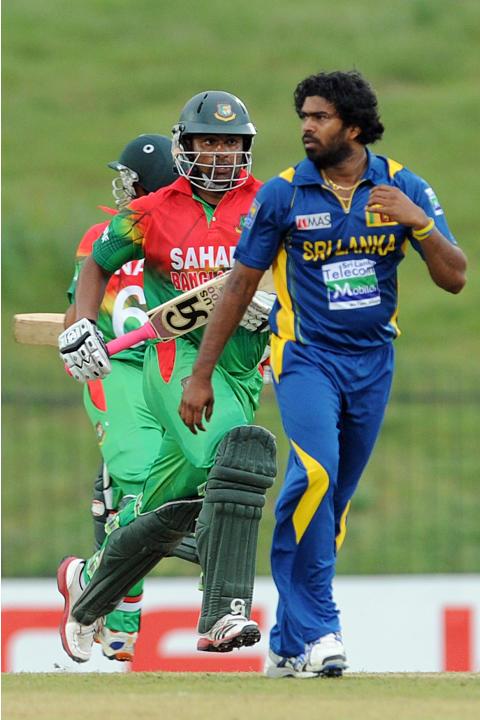 Bangladeshi cricketer Tamim Iqbal (C) runs between the wickets as Sri Lankan cricketer Lasith Malinga looks on during the opening one-day international (ODI) match between Sri Lanka and Bangladesh at