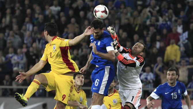 Greece's Alexandros Tziolis, center, and Romania's Ciprian Andrei Marica, left, and goalkeeper Bogdan Ionut Lobont jump for the ball during their World Cup qualifying playoff first leg soccer match at the Karaiskaki stadium in the port of Piraeus, near Athens, Friday, Nov. 15, 2013. Greece won 3-1