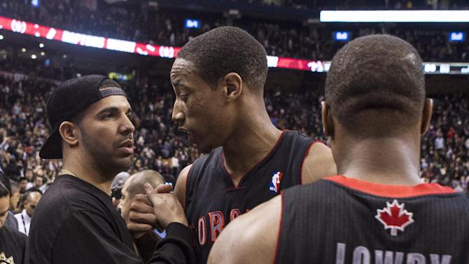Rapper Drake, left, congratulates Toronto Raptors DeMar DeRozan, center, after his team's 96-80 win over Brooklyn Nets during an NBA basketball game, Saturday, Jan. 11, 2014 in Toronto
