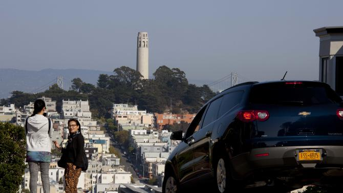 "In this photo taken Thursday, Sept. 27, 2012, people pose for pictures and a car makes its way down Lombard Street with Coit Tower on Telegraph Hill in the background in San Francisco. San Francisco has a long history as a favorite site for filmmakers and the movie buffs who want to see the spots where their favorite scenes took place, from Fort Point under the Golden Gate Bridge where Jimmy Stewart saved Kim Novak in ""Vertigo"" to the steps of City Hall, where Sean Penn gave an impassioned speech in ""Milk,"" to Alcatraz, stage for Clint Eastwood and many others. (AP Photo/Eric Risberg)"