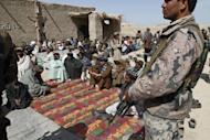 Afghan men gather for a ceremony at a mosque in Alokozai village of Pajwayi district in Kandahar province on March 13, 2012. Gunmen on Tuesday attacked the memorial service for 16 villagers killed by a US soldier, shooting dead a member of the Afghan military and wounding a policeman in a hail of gunfire