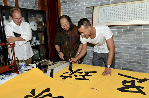 "Premier League team Chelsea's Terry of England writes Chinese character of ""soccer"" with a brush as he imitates a work by a calligrapher, at a museum in Guangzhou"