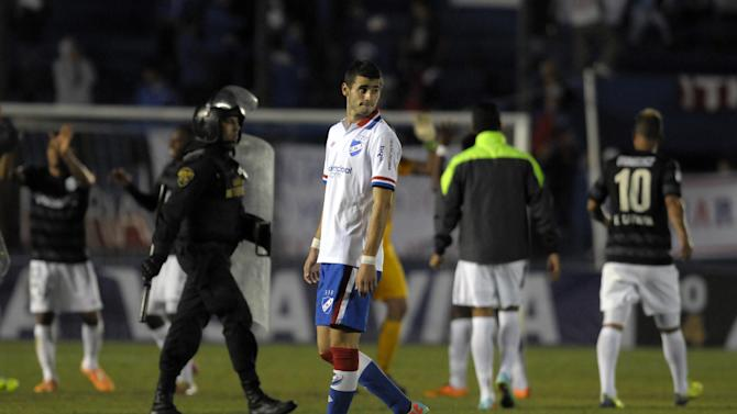 Gaston Pereiro of Uruguay's Nacional, center, walks from the pitch after loosing a Copa Libertadores soccer game against Colombia's Atletico Nacional in Montevideo, Uruguay, Tuesday, March 18, 2014. Atletico Nacional won the match 1-0