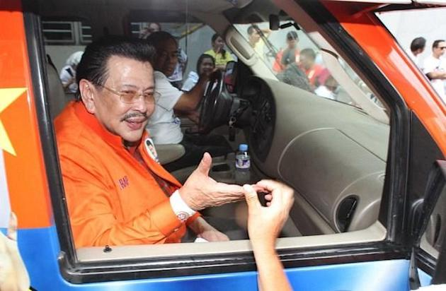 Former President Joseph Estrada greets supporters after filing his certificate of candidacy for Manila mayor at the Commission on Elections office in Arroceros Street Oct. 2. (Mike Alquinto, NPPA Images)