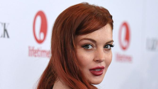 "FILE - In this Nov. 20, 2012 photo, actress Lindsay Lohan attends a dinner celebrating the premiere of ""Liz & Dick"" at the Beverly Hills Hotel in Beverly Hills, Calif. Lohan is under arrest and charged with third-degree assault Thursday, Nov. 29, 2012 after police say she hit a woman during an argument at a New York City nightclub. (Photo by John Shearer/Invision/AP, File)"
