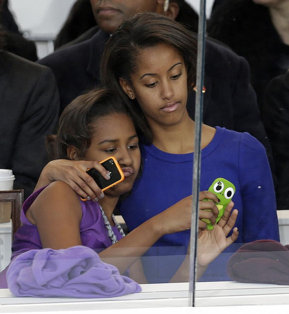 Malia Obama, right, and Sasha Obama look on from the presidential box during the Inaugural parade, Monday, Jan. 21, 2013, in Washington. Thousands  marched during the 57th Presidential Inauguration pa