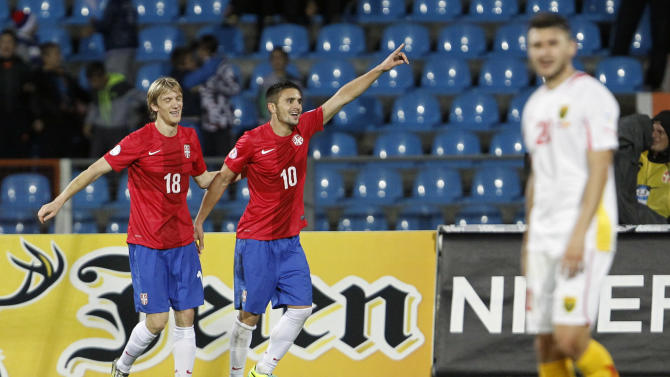 Serbia's Dusan Tadic, center and Dusan Basta celebrate his goal during their World Cup 2014 Group A qualifying soccer match against Macedonia, at the City Stadium in Jagodina, Serbia, Tuesday, Oct. 15, 2013