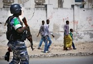 Picture taken by the African Union-United Nations Information Support Team shows a Ugandan police officer with the African Union Mission in Somalia (AMISOM) on patrol in Mogadishu, November 9, 2012. At least six people were killed when a suicide bomber blew himself up amongst a group of security officials outside the Somali prime minister's office on Tuesday, army officials said
