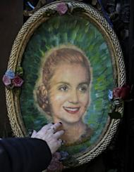 A woman touchs a portrait of Eva Duarte de Peron at the Duarte's Family vault where rest the remains of Eva Duarte de Peron on the 60th anniversary of her death in Buenos Aires