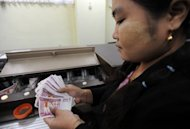 A Myanmar employee handles bank notes at the central bank in Yangon in June 2012. A US ban on all Myanmar imports is stifling key job-creating areas of the economy such as the garment industry rather than hurting the interests of the corrupt elite it targets, a report said Friday