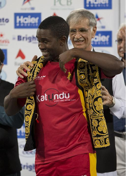 Pakistani chief minister Pervez Khattak help Zimbabwean captain Elton Chigumbura wear traditional Pakistani waistcoat presented to him after a match  at the Gaddafi Stadium in Lahore, Pakistan, Sunday