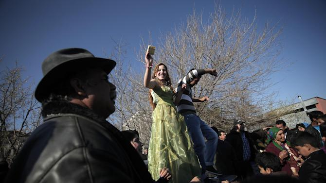 """This Saturday, March 23, 2013  photo shows Roma girl and boy from the Kalaidzhi community dancing on the trunk of a car, holding money in their hands during so called """"Roma bridal market"""". The Kalaidzhi, who represent only a small portion of the estimated 700,000 Roma in Bulgaria, are almost all devout Orthodox Christians who keep teenage boys and girls separate. Parents sometimes remove girls from school at 15 or even earlier to keep them from mixing with boys. The isolation is broken only by Internet chats and the twice-a-year bridal fairs.  (AP Photo/Valentina Petrova)"""