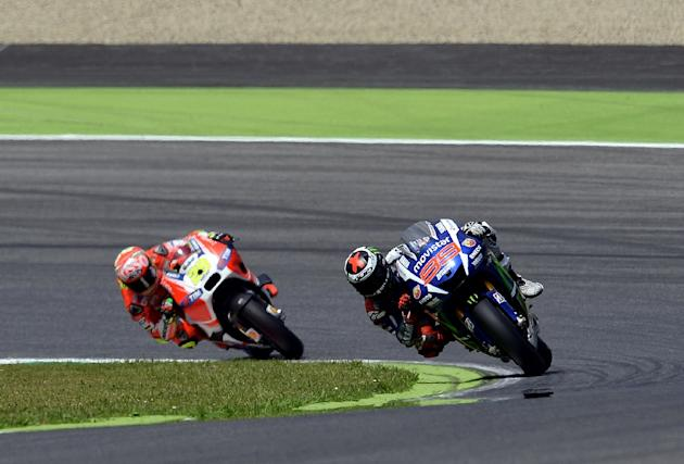 Italian rider Andrea Iannone (L) follows with his Ducati spanish Jorge Lorenzo on Yamaha during the qualifing session of the Italian Grand Prix at the Mugello racetrack on May 30, 2015