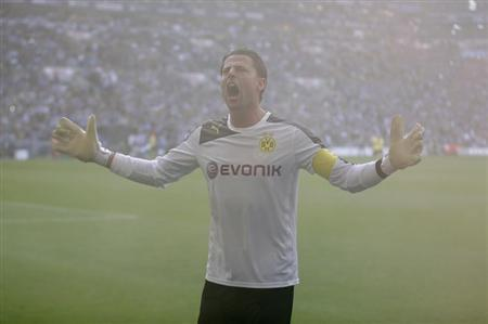 Borussia Dortmund's Weidenfeller tries to calm down his team's supporters before his team's German first division Bundesliga soccer match against Schalke 04 at the Schalke Arena in Gelsenkirchen