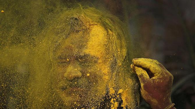 An Indian, face smeared with colored powder, celebrates Holi festival in Gauhati, India, Wednesday, March. 27, 2013. Holi, the Hindu festival of colors that also marks the advent of spring, is being celebrated across the country Wednesday. (AP Photo/Anupam Nath)