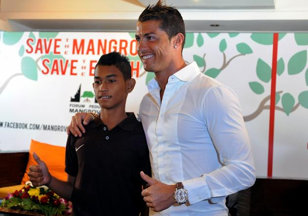 Christiano Ronaldo (R) is reunited with Martunis, an Indonesian survivor of the deadly 2004 Aceh tsunami who the Real Madrid star met in 2005 during a mission to assist tsunami victims, in Kuta on Jun