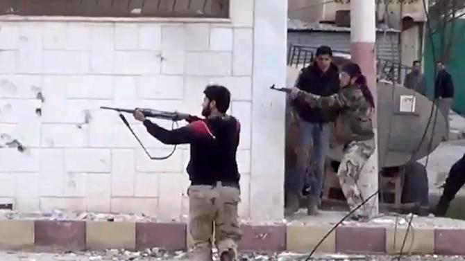 In this image taken from video obtained from the Shaam News Network, which has been authenticated based on its contents and other AP reporting, Free Syrian Army fighters fire at Syrian army soldiers during a fierce firefight in Daraa al-Balad, Syria, Monday March 18, 2013. Two years after the anti-Assad uprising began, the conflict has become a civil war, with hundreds of rebel group fighting Assad's forces across Syria and millions of people pushed from their homes by the violence. The U.N. says more than 70,000 people have been killed. (AP Photo/Shaam News Network via AP video)