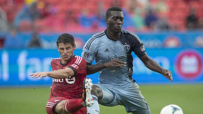 Toronto FC 's Mark Bloom, left, clears the ball under pressure from Sporting Kansas City's C.J. Sapong during the second half of an MLS soccer game in Toronto on Saturday, Sept, 21, 2013