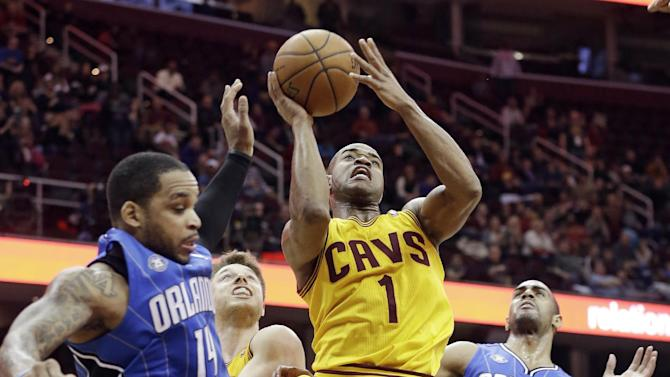 Cleveland Cavaliers' Jarrett Jack (1) shoots  between Orlando Magic's Jameer Nelson (14) and Arron Afflalo (4) during overtime in an NBA basketball game Thursday, Jan. 2, 2014, in Cleveland. The Cavaliers won 87-81
