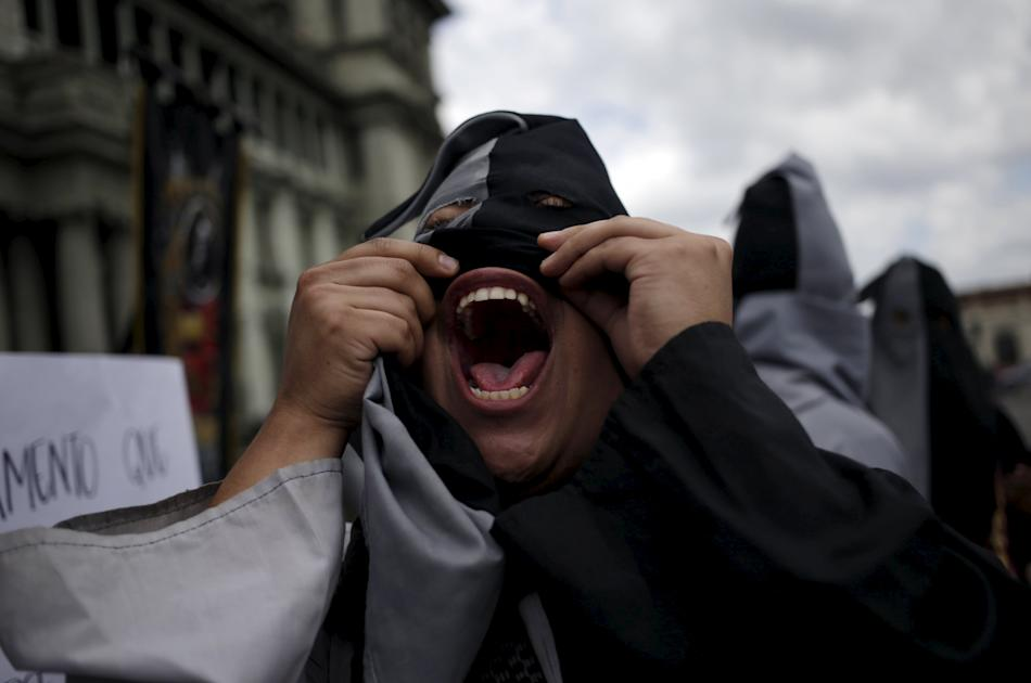 Hooded student of the San Carlos University of Guatemala shouts slogans during a demonstration against the government of the Guatemalan President Perez Molina, in Guatemala City