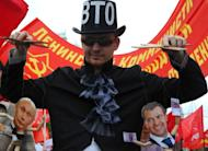 A Communist Party supporter holds puppets depicting Russian President Vladimir Putin (left) and Prime Minister Dmitry Medvedev (right) at a rally in Moscow last week against Russia's impending membership of the World Trade Organization