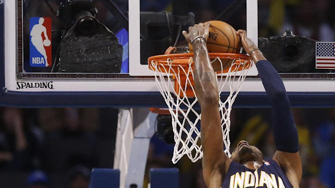 Indiana Pacers forward Paul George (24) dunks in front of Oklahoma City Thunder forward Serge Ibaka (9) in the first quarter of an NBA basketball game in Oklahoma City, Sunday, Dec. 8, 2013