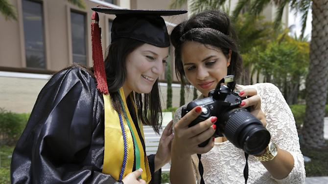 "In this April 29, 2014 photo, University of South Florida graduating seniors Kyra Ciotti, 22, of Tampa, Fla., left, and Rita Sibaja, 24, of Winter Haven, Fla., look at photos that Rita took of Kyra in her cap and gown Tuesday, April 29, 2014, in Tampa, Fla. The university has banned all self portraits, also known as ""selfies,"" during their 2014 graduation exercises. (AP Photo/Chris O'Meara)"