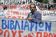 Greek construction workers stand behind banners in front of the labour ministry in Athens on April 4 during their protest against the austerity measures and the unemployment in their sector. The eurozone debt crisis delivered more bad news on Monday with data showing record high unemployment of 11.1 percent and a manufacturing outlook at its lowest levels for three years